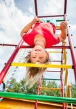 Little girl hanging from a jungle gym playing in a summer garden - child risky play concept royalty free stock photography