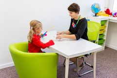 Free Elementary Age Girl In Child Occupational Therapy Session Doing Playful Exercises With Her Therapist. Stock Photography - 160354132