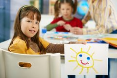 Elementary age girl with painting at school. Portrait of elementary age schoolgirl showing colorful paining to camera in art class in primary school classroom Royalty Free Stock Images