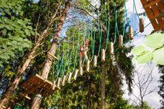 Little girl on a ropes course in a treetop adventure park passing hanging rope obstacle royalty free stock images