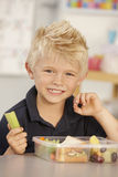 Elementary Age Schoolboy Eating Healthy Packed Lunch In Class Stock Photos