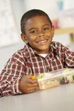 Elementary Age Schoolboy Eating Healthy Packed Lunch In Class Stock Images