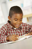 Elementary Age Schoolboy Reading Book In Class Stock Photo