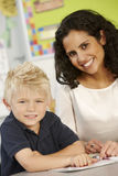 Elementary Age Schoolboy Reading Book In Class With Teacher Royalty Free Stock Image