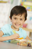 Elementary Age Schoolgirl Eating Healthy Packed Lunch In Class Stock Image