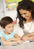Elementary Age Schoolgirl Reading Book In Class With Teacher Stock Photo