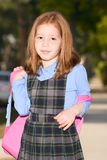 Elementary age schoolgirl in uniform with backpack Stock Photo