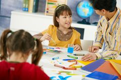 Elementary age schoolgirls painting. Elementary age children sitting around desk enjoying painting with colors in art class in primary school classroom Royalty Free Stock Image