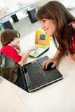 Elementary aged boy and teenage girl using laptops Stock Photo