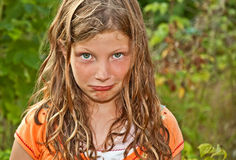 Elementary Aged Girl Making Pouty Face. This elementary aged Caucasian girl is playing outdoors and making a goof pouty face.  Her hair is tangled and wind blown Royalty Free Stock Images