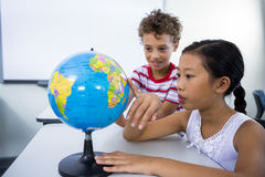 Elementary boy and girl looking at glob in classroom Royalty Free Stock Photography