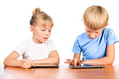 Elementary boy and girl at table with pads Stock Photo