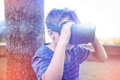 Elementary boy looking through virtual reality headset in school library Stock Image