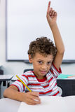 Elementary boy raising hand in classroom. Portrait of elementary boy raising hand in classroom Stock Photography