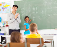 Elementary chinese applauding. Elementary school teacher applauding after young girl wrote chinese words on blackboard Royalty Free Stock Photo