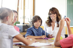 Elementary classroom setting. Focus on school boy. Royalty Free Stock Image