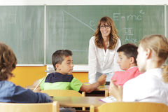 Elementary classroom setting. Focus on teacher and chalkboard. Stock Photography