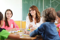 Elementary classroom setting. Focus on teacher and chalkboard. Royalty Free Stock Photos