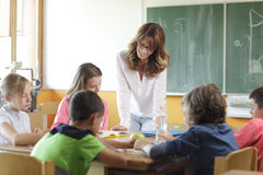 Elementary classroom setting. Focus on teacher and chalkboard. Stock Photos