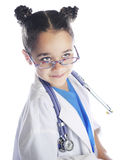 Elementary. Close-up image of a cute elementary doctor looking over the top of her glasses.  She wears scrubs and a lab coat with a stethoscope drapped around Royalty Free Stock Photography