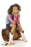 Elementary Cowrgirl. An elementary cowgirl looking at the viewer while sitting on an old wooden barrel.  On a white background Royalty Free Stock Photography