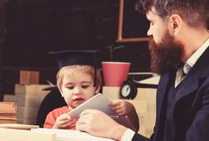 Elementary education concept. Kid studies with teacher, listening with attention. Teacher and pupil in mortarboard stock images