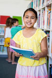 Elementary girl holding books in school library Royalty Free Stock Photography