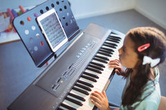 Elementary girl looking at digital tablet on stand while practicing piano. In class at school Stock Photos