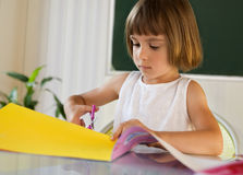 Elementary pupil with colorful paper and scissors Stock Photo