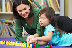 Elementary Pupil Counting With Teacher In Classroom. Lying Down Smiling Stock Images
