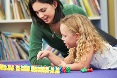 Elementary Pupil Counting With Teacher In Classroom. Lying Down Talking Royalty Free Stock Photo