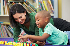 Elementary Pupil Counting With Teacher In Classroom. Talking To Each Other Royalty Free Stock Image
