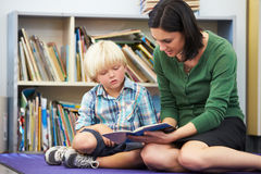Elementary Pupil Reading With Teacher In Classroom. Sitting Down Stock Photography
