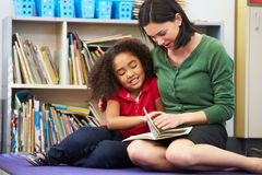 Elementary Pupil Reading With Teacher In Classroom. Sitting Down Stock Image