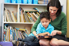 Elementary Pupil Reading With Teacher In Classroom. Sitting Down Pointing At Book Royalty Free Stock Photos