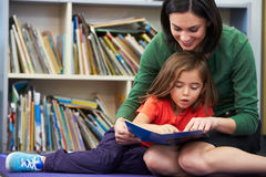 Elementary Pupil Reading With Teacher In Classroom. Sitting Down Smiling Royalty Free Stock Image