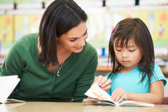 Elementary Pupil Reading With Teacher In Classroom. Sitting At Table Stock Photography