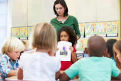 Elementary Pupil Showing Drawing To Classmates In Classroom. Standing Still Stock Photos