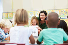 Elementary Pupil Showing Drawing To Classmates In Classroom. With Teacher Smiling Stock Image