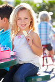 Elementary Pupil Sitting At Table Eating Lunch. Holding Snack Smiling Royalty Free Stock Photos