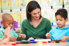 Elementary Pupils Counting With Teacher In Classroom. Having Fun Smiling Royalty Free Stock Photography