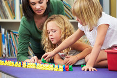 Elementary Pupils Counting With Teacher In Classroom Royalty Free Stock Image