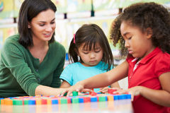 Elementary Pupils Counting With Teacher In Classroom. Sitting at Table Royalty Free Stock Photo