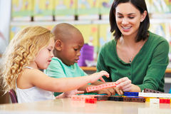 Elementary Pupils Counting With Teacher In Classroom. Sitting At Table Having Fun Stock Images