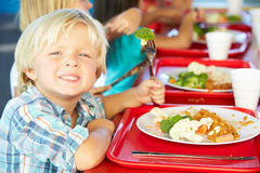 Elementary Pupils Enjoying Healthy Lunch In Cafeteria. Holding Fork Smiling To Camera Royalty Free Stock Photos