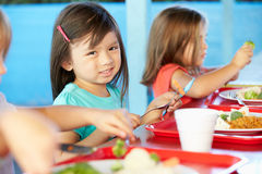 Elementary Pupils Enjoying Healthy Lunch In Cafeteria Royalty Free Stock Photography