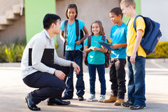 Elementary pupils teacher. Cute elementary pupils outside classroom talking to teacher stock photo