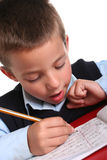 Elementary School boy. Young boy in elementary/primary school uniform working. Isolated. Copyspace Royalty Free Stock Photo