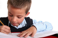 Elementary School boy. Young boy in elementary/primary school uniform working. Isolated. Copyspace Royalty Free Stock Photos