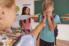 Elementary school. Boy is bullying by children at school Royalty Free Stock Photos